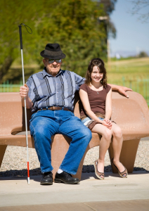 Picture of an older man sitting on a park bench holding a long white cane. Seated to his left is a younger female, possibly his granddaughter.